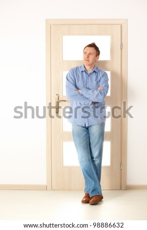 Attractive thoughtful man standing near door, designer or architect planning furnishings - stock photo