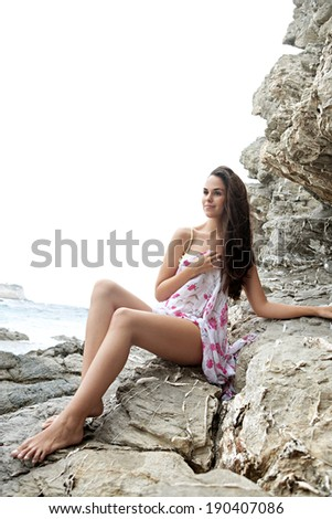 Attractive thoughtful woman relaxing on a coastal textured rock mountain wrapped in a floral sarong, sunbathing and relaxing during a summer holiday trip by the sea. Beauty and health lifestyle. - stock photo