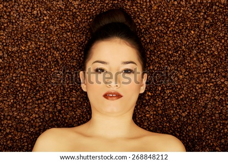 Attractive topless woman lying in coffee grains. - stock photo