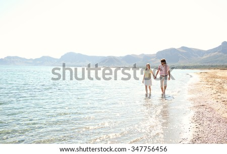 Attractive tourist couple on holiday walking along the sea shore holding hands on vacation, blue sky with sun light, outdoors space. Romance and dynamic honeymoon calm lifestyle, summer exterior. - stock photo