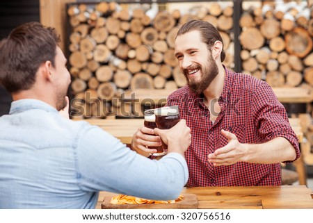 Attractive two guys are drinking beer in bar. They are sitting at the table opposite each other. The friends are clinking glasses. They are talking and smiling - stock photo