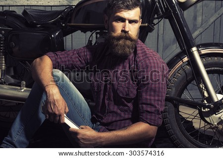 Attractive unshaven male biker in purple checkered shirt and jeans sitting near motorcycle in garage holding metallized iron spanner looking forward on workshop background, horizontal picture - stock photo