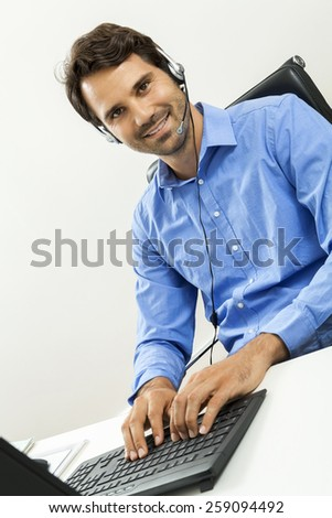 Attractive unshaven young man wearing a headset offering online chat and support on a client services of help desk as he types in information on his computer - stock photo