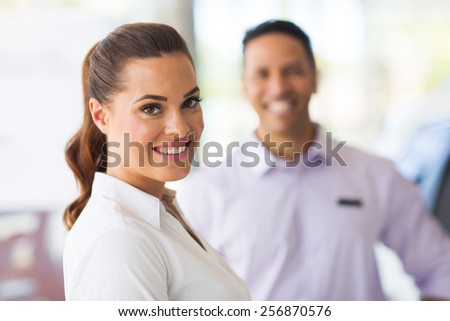 attractive vehicle sales woman standing in front of colleague - stock photo