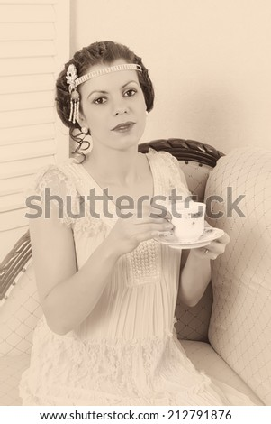 Attractive vintage 1920s woman sitting on a chaise longue - stock photo