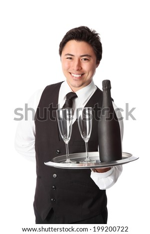 Attractive waiter with bottle and glasses, wearing a black vest. White background. - stock photo
