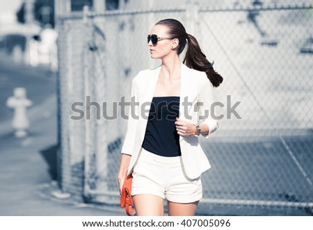 Attractive well dressed young woman walking across the street. (Fashion concept) - stock photo