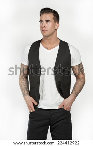 Attractive white athletic male model wearing a trendy white t-shirt with a black vest and black pants posing in a studio on a white background while looking to the left with his hands in his pockets. - stock photo