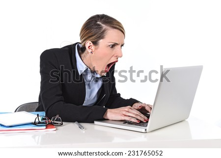 attractive white blond businesswoman sitting at office desk working with laptop in stress looking upset and dealing work issues screaming shouting at computer - stock photo