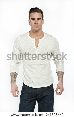 Attractive white caucasian male model wearing a white casual shirt and modern jeans posing in a studio on a white background while looking at the camera. - stock photo