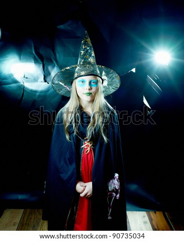 Attractive witch girl in spooky robe and hat