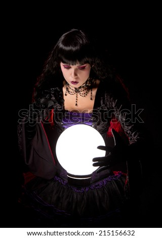 Attractive witch or fortune teller looking into a crystal ball, Halloween theme   - stock photo