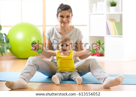Attractive woman and her child boy exercising with dumbbells at home