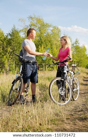 Attractive woman and man refreshing after biking in green environment - stock photo
