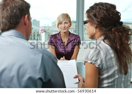 Attractive woman applicant talking during job interview. Over the shoulder view. - stock photo