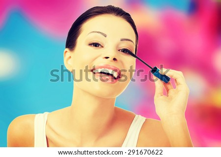 Attractive woman applying make up - stock photo