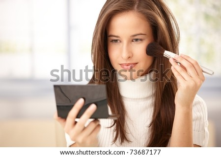 Attractive woman applying makeup with brush, checking in pocket mirror, smiling.?