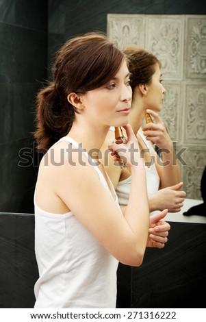 Attractive woman applying parfume in the bathroom. - stock photo