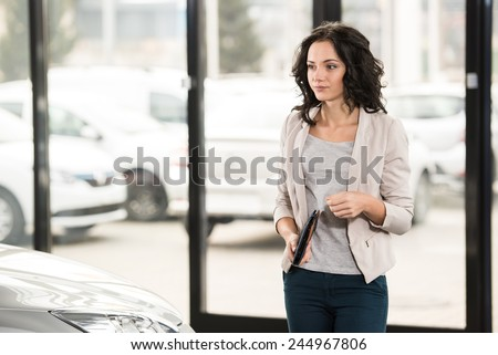 Attractive woman at car salon is choosing a car. - stock photo