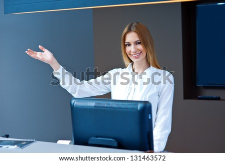 attractive woman at reception desk looking at camera and making friendly welcome gesture - stock photo