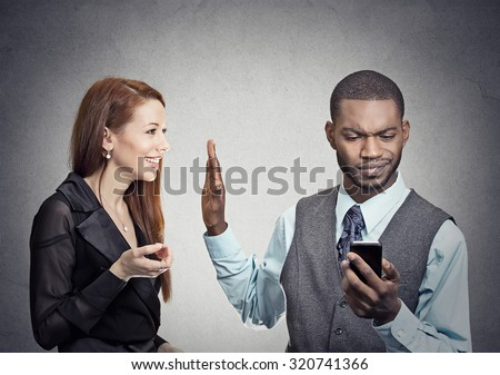 Attractive woman being ignored stopped by young handsome man looking at smartphone reading browsing internet isolated on gray wall background. Phone addiction concept. Human face expression emotions  - stock photo