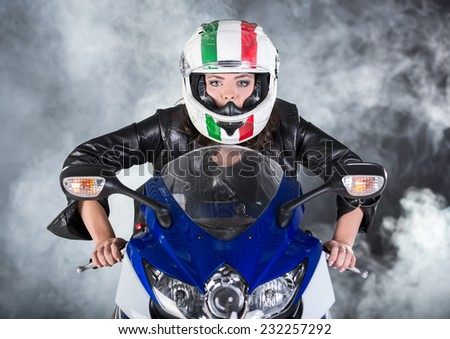 Attractive woman biker is posing on motorcycle with helmet. Dark and foggy background. - stock photo