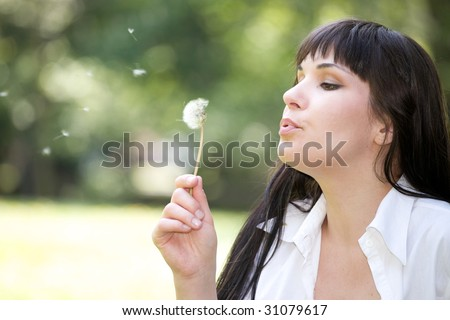 attractive woman bloweing dandelion at meadow - stock photo