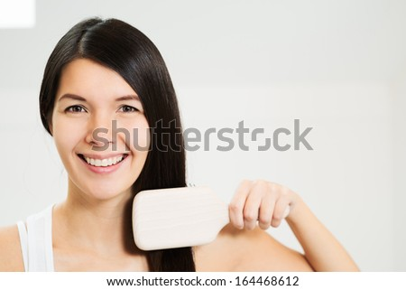 Attractive woman brushing her hair looking at the camera with a friendly charming smile