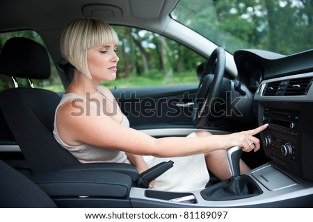 attractive woman changing radio station in the car - stock photo