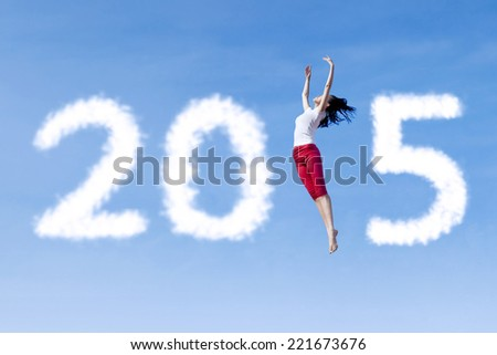 Attractive woman dancing on the sky and forming number 2015 - stock photo