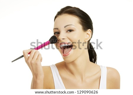 Attractive woman doing make-up on face. Isolated - stock photo