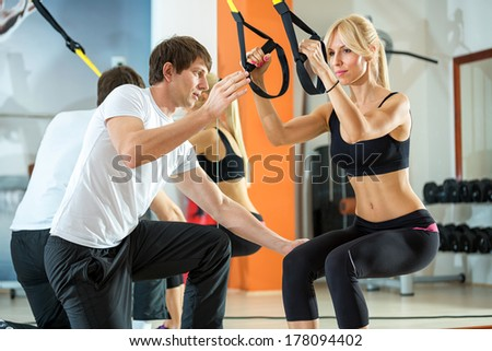 attractive woman doing suspension training with fitness straps - stock photo