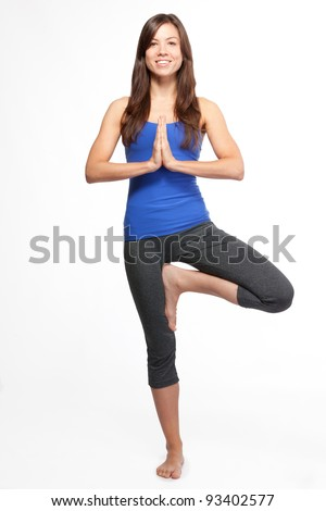 Attractive woman doing yoga tree pose - stock photo