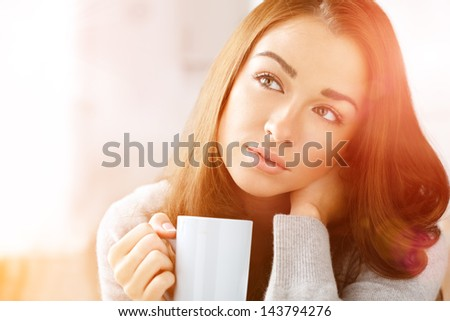 Attractive woman drinking coffee at home - stock photo