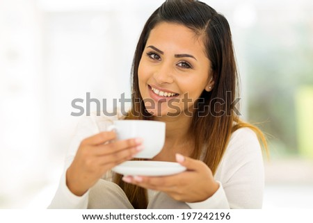 attractive woman drinking coffee in bedroom