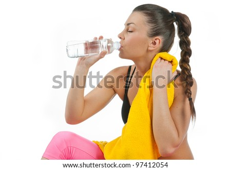 attractive woman drinking water from bottle after exercise