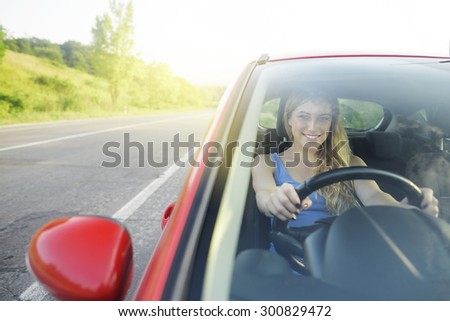 Attractive woman driving a new car on the highway outside the city. - stock photo