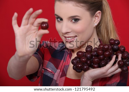 Attractive woman eating grapes - stock photo