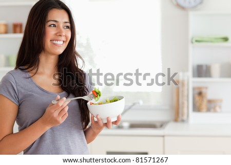 Attractive woman enjoying a bowl of salad while standing in the kitchen - stock photo