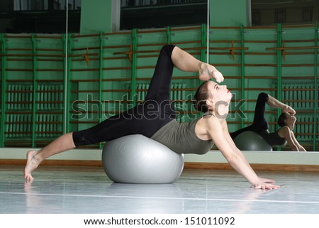 Attractive woman exercising with exercise ball at dance hall - stock photo