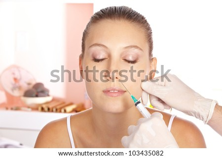 Attractive woman getting a wrinkle treatment with a syringe - stock photo
