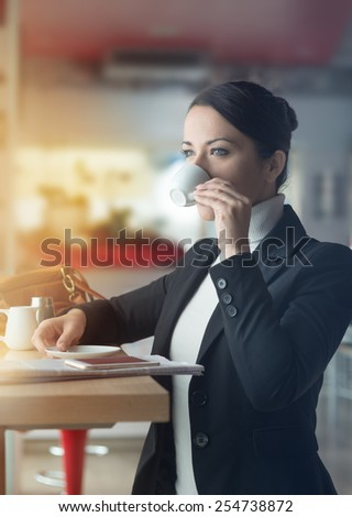 Attractive woman having a coffee break at the bar, she is drinking a cup of coffee and staring at the window - stock photo