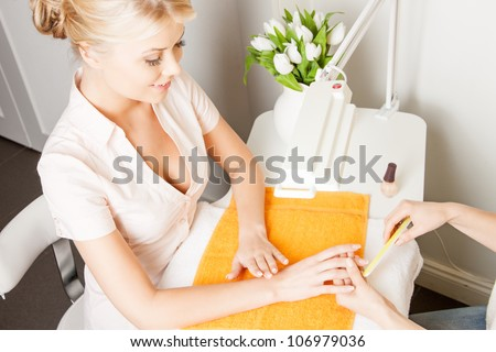 attractive woman having a manicure at the salon - stock photo