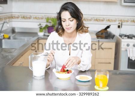 Attractive woman having breakfast in kitchen interior - stock photo