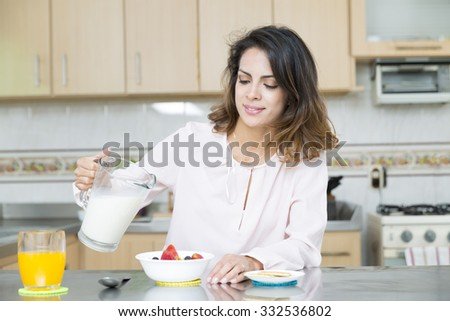 Attractive woman having breakfast in kitchen interior - stock photo