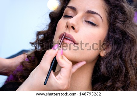 attractive woman having lip gloss make up applying in salon - stock photo