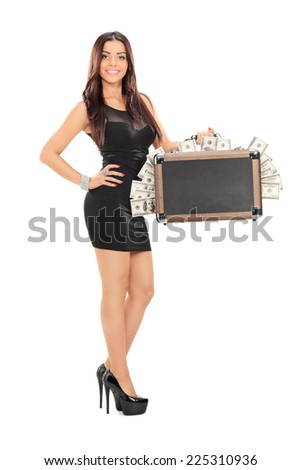 Attractive woman holding a suitcase full of money isolated on white background - stock photo