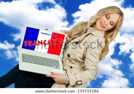 attractive woman holding laptop with french language sign on the screen - stock photo