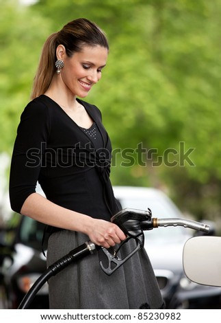 attractive woman holding nozzle at gas station - stock photo