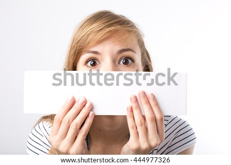 Attractive woman holding paper blank in her hands. Portrait of emotional young woman showing surprised and happy emotions - stock photo